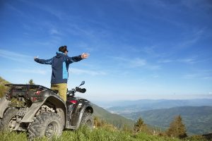 Man on ATV with arms spread wide