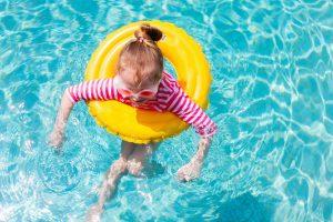 little girl in pool wearing rash guard